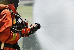 Firemen using extinguisher and water from hose for fire fighting in firefight training. Firefighter wearing fire suit for protect and safety under danger case.This team is under civil service system.