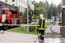 Firemen wearing uniform standing behind fire tape and many fire engine trucks with ladder at accident in highrise tower residential or office building in city center. Emergency rescue at disaster
