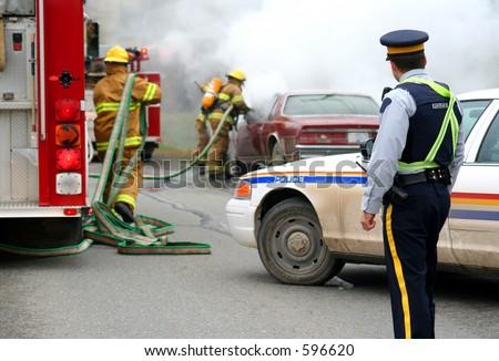 firemen with burning car - stock photo