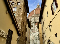 FIRENZE, ITALY. Date of photo is 26.09.2015. Fragment of facade of medieval buildings in Florence. Duomo Santa Maria del Fiore, stone old and yellow painted houses. Blue sky. Marble cathedral, cupola.