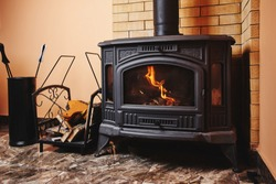 Fireplace and accessories in black with a fire burning inside. Stylish interior, giving warmth in the house.