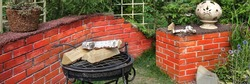 Fireplace and Grill  in Landscaped Garden on Family Private Corner. Modern Backyard With BBQ Grill and Decorative Retaining Brick Wall. Modern Landscaped Backyard Design.
