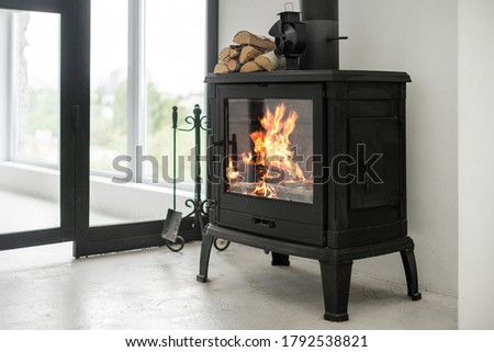 Fireplace at lounge room standing on concrete floor with copy space. Home with modern interior, wooden log on top of fireside and equipment against white wall Stock fotó ©