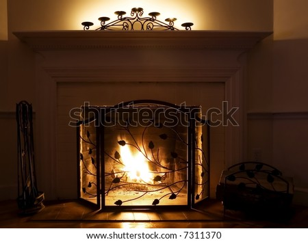 Fireplace with burning logs and candles on the mantle