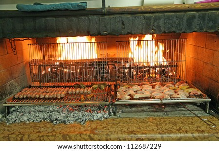 fireplace with hearth and grilled meat over an open fire