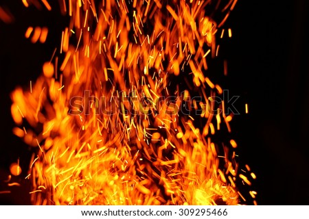 Firestorm texture. Bokeh lights on black background, shot of flying fire sparks in the air