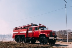 Firetrucks parked in open field in rural countryside on sunny day.