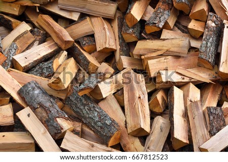 Firewood background - chopped firewood on a stack. Dry chopped firewood logs in a pile.  #667812523
