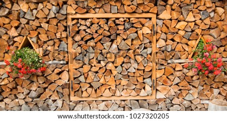 Firewood for the winter, stacks of firewood, pile of firewood with flowers in summer background. #1027320205