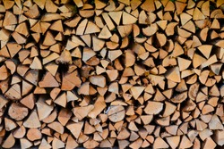 Firewood pile stacked chopped wood trunks for winter heating fireplace