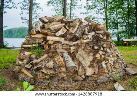firewood piled in one pile outdoors against the backdrop of nature #1428887918