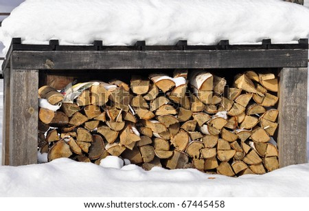Firewood stacked in winter - stock photo