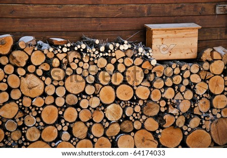 Firewood stock of round tree trunks near the wall with post box