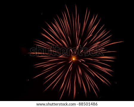 Firework at night. Single red, orange and yellow burst - black sky, long exposure