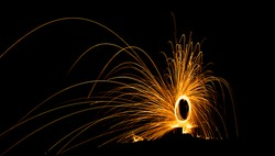 Firework showers of hot glowing sparks from spinning steel wool on the ground. (Long Exposure)
