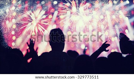 Fireworks and crowd celebrating the New year - retro styled photo #329773511