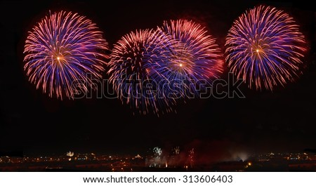 Fireworks. Colorful violet fireworks in Malta, dark sky background and house light in the far, Malta fireworks festival, 4 of July, Independence day, New Year, maltese fireworks.Zurrieq, Malta