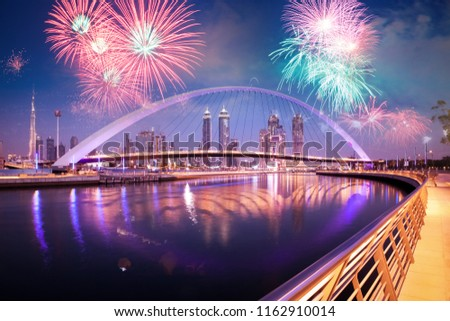 fireworks display over Dubai Downtown skyscrapers and the newly built Tolerance bridge as viewed from the Dubai water canal.