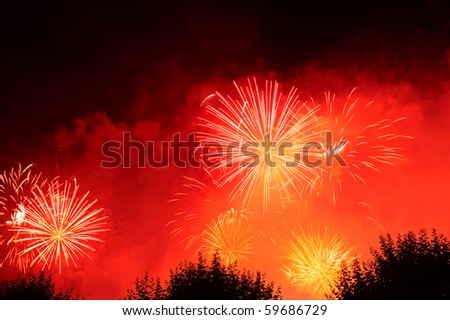 Fireworks exploding in the night sky against a background of red smoke. Space for text in the dark of the night sky. - stock photo