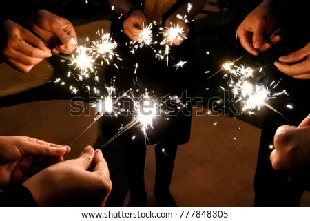Fireworks illuminate in the dark for celebration. Friends are standing around the fireworks with a precious moment and friendship. #777848305