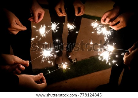 Fireworks illuminate in the dark for celebration. Friends are standing around the fireworks with a precious moment and friendship. #778124845