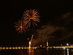 Fireworks in Bordeaux: golden fireworks explosions over the Garonne river in Bordeaux old city at night, France 2019