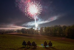 Fireworks in night sky with silhouette of people in lawn chairs in foreground and forest with trees in background.