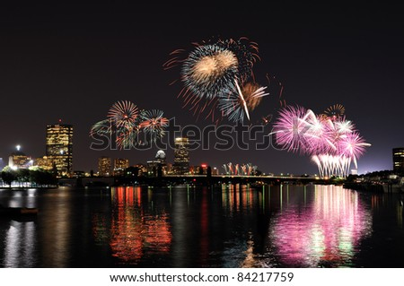 Fireworks over Boston and its reflections on Charles River
