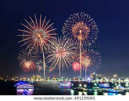 Fireworks over cityscape by the beach and sea surrounding with hotels, restaurant, and service boats and cruises during blue twilight time for celebrating New Year eve and special occasion on holidays #691239085