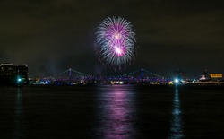 Fireworks over the Ben Franklin Bridge in Philadelphia, PA, reflecting in the water of the Delaware River.