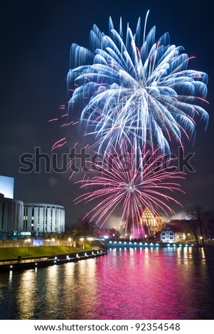Fireworks over the river in the city - stock photo