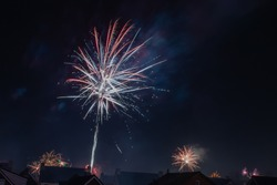 Fireworks over the roofs of houses