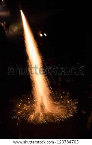 Fireworks rocket being launched out of a champagne bottle on its way into the sky