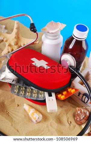 first aid box with medicines,thermometer and stethoscope on the beach as healthy summer holiday concept