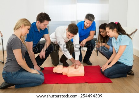 First Aid Instructor Showing Resuscitation Technique On Dummy