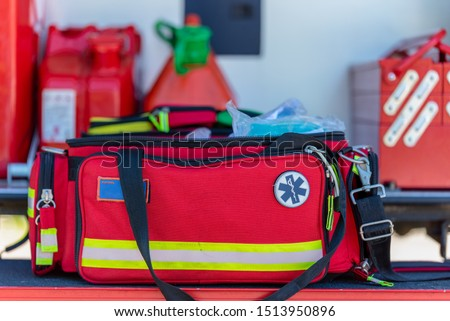 First aid kit an open  red first aid kit bag with a black zip and handle, in closeup. and handle in closeup in an open fire truck