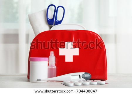 First-aid kit and medicines on the table in the background of the window. #704408047