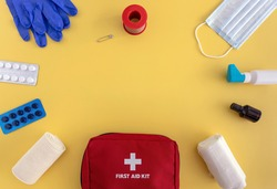 first aid kit-bandages, band-aid, tablets, medical gloves, face mask, spray on a yellow background