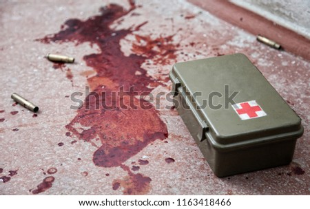 First aid kit metal box lying on floor with empty bullet shells and fresh stains of human blood around. Emergency medical care for gunshot wounds, bleeding stop, tactical combat casualty care concept