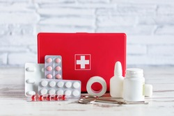 First aid kit red box with medical equipment and medications for emergency on white wooden background over brick wall.