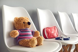 First-aid kit, stethoscope and cute teddy bear on white chairs in waiting room of children's medical center or pediatric clinic. Concept of kids' visit to hospital to see pediatrician or family doctor