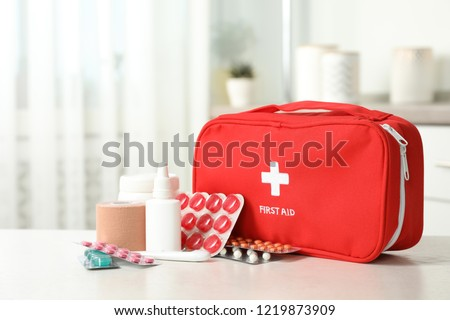 First aid kit with pills on table indoors #1219873909
