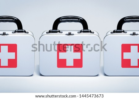 First aid kits with cross emblems in a row on light grey background #1445473673