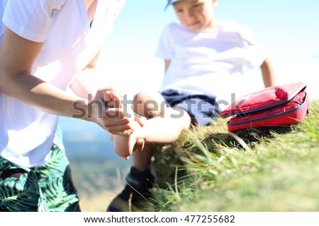 First aid, twisted leg. The child twisted his ankle during a mountain tour. Wound broken leg.