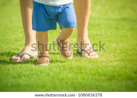 First baby steps.  Closeup of babies feet walking with mothers help.