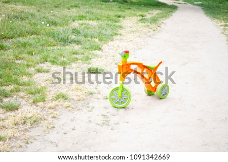 first bicycle without pedals for the youngest. Orange plastic bicycle on a glade and a path #1091342669