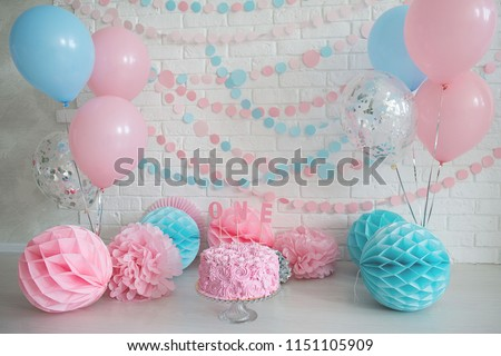 First birthday cake. Smash cake. One year. Pink and blue photo zone with paper garlands, balloons, paper honeycombs and pink cream cake.
