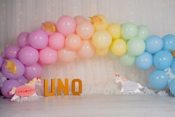 First birthday smashcake photo session with a rainbow of balloons and unicorns in a photo studio