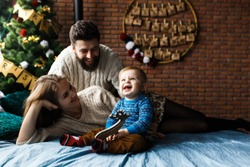 First Christmas. Happy baby boy receives a gift from Santa Claus for the first time. Cheerful emotions parents and baby. Baby sitting on bed, Christmas tree and decorations on background.