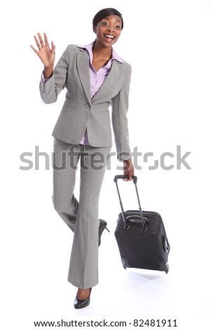 First class business travel for a happy beautiful young african american woman wearing a smart grey suit, waving in greeting while pulling her suitcase.